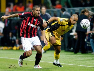 AC Milan Rino Gattuso challenges Julio Cesar of AEK Athens during Champions League Clash (Image from REUTERS/Alessandro Garofalo)